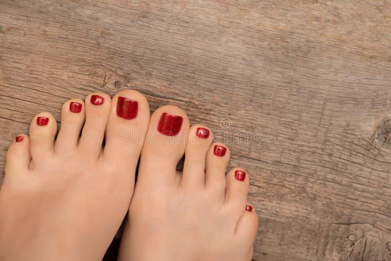 Όμορφα θηλυκά πόδια με το κόκκινο pedicure στο ξύλινο υπόβαθρο στοκ φωτογραφία