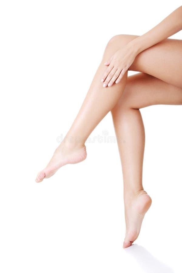 Όμορφα θηλυκά πόδια που αγγίζονται με το χέρι στοκ εικόνα με δικαίωμα ελεύθερης χρήσης
