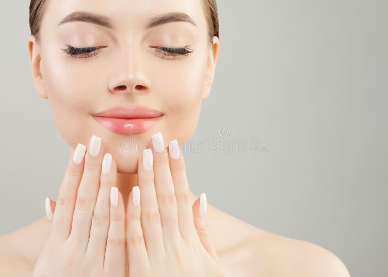 Όμορφα θηλυκά χέρια με τα άσπρα καρφιά ενάντια στα ρόδινα χείλια makeup Έννοια μανικιούρ στοκ φωτογραφίες