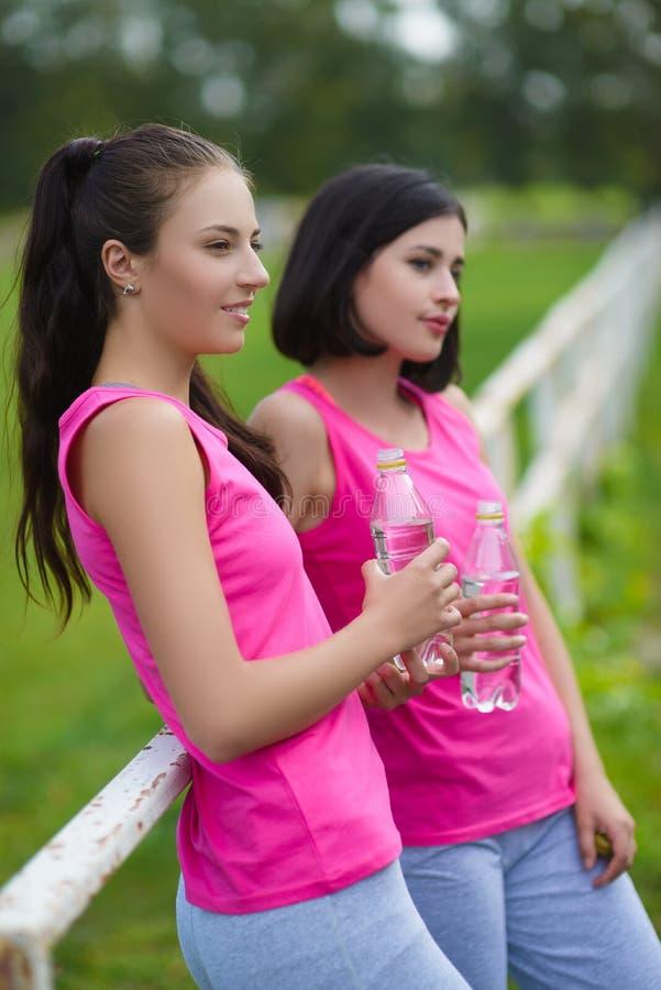 Όμορφα κορίτσια αθλητών ικανότητας που στηρίζονται ή πόσιμο νερό υπαίθριο στοκ εικόνες