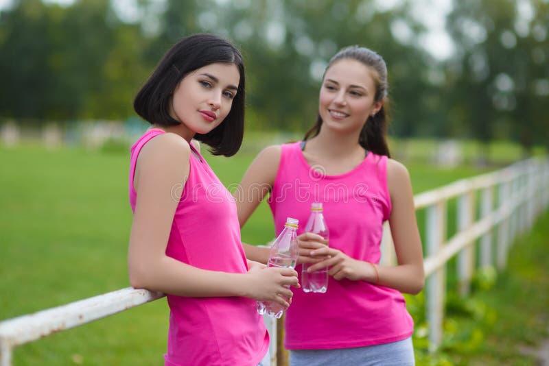 Όμορφα κορίτσια αθλητών ικανότητας που στηρίζονται ή πόσιμο νερό υπαίθριο στοκ φωτογραφίες