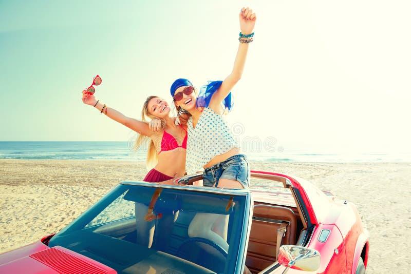 Όμορφα κορίτσια κομμάτων που χορεύουν σε ένα αυτοκίνητο στην παραλία στοκ εικόνα