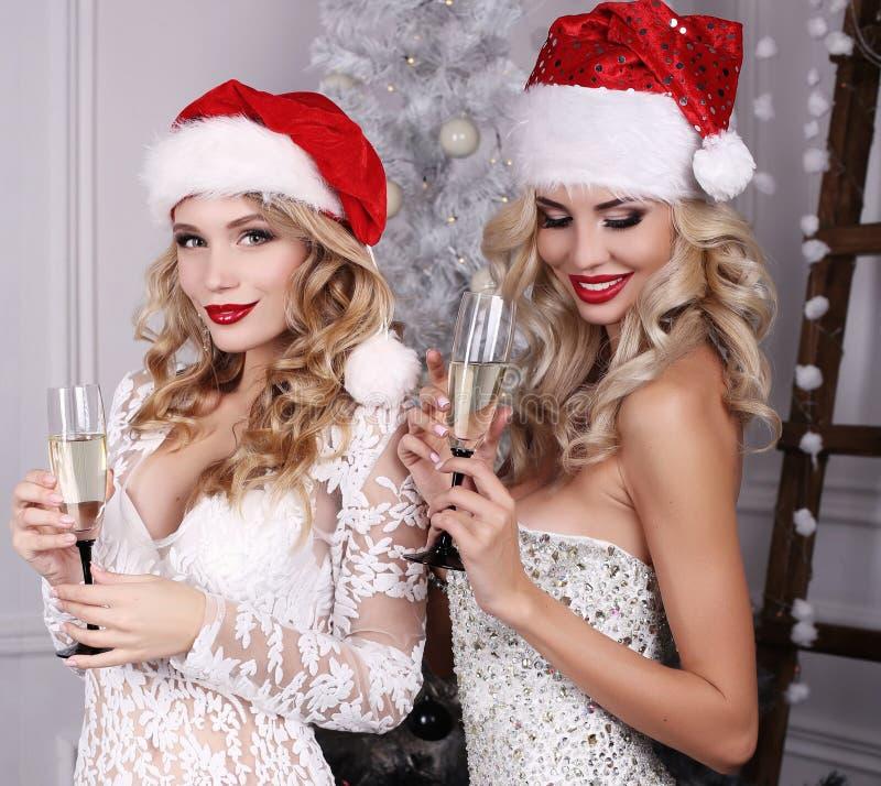 Όμορφα κορίτσια με την τοποθέτηση ξανθών μαλλιών εκτός από το χριστουγεννιάτικο δέντρο στοκ φωτογραφίες
