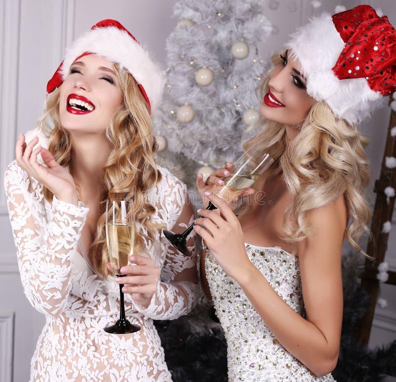 Όμορφα κορίτσια με την τοποθέτηση ξανθών μαλλιών εκτός από το χριστουγεννιάτικο δέντρο στοκ εικόνα με δικαίωμα ελεύθερης χρήσης