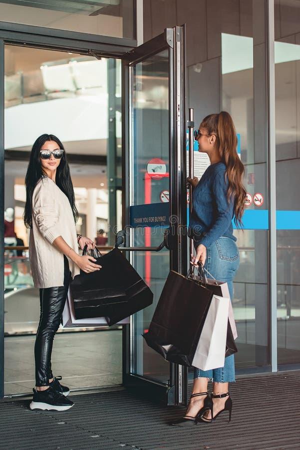 Όμορφα κορίτσια με τις τσάντες εγγράφου κοντά στην είσοδο στην υπεραγορά στοκ φωτογραφία