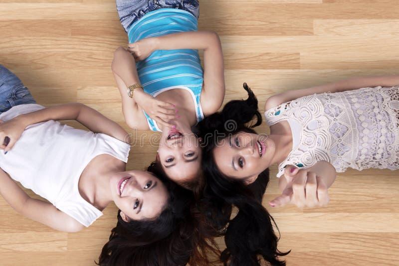 Όμορφα κορίτσια που ξαπλώνουν στο ξύλινο πάτωμα στοκ εικόνες