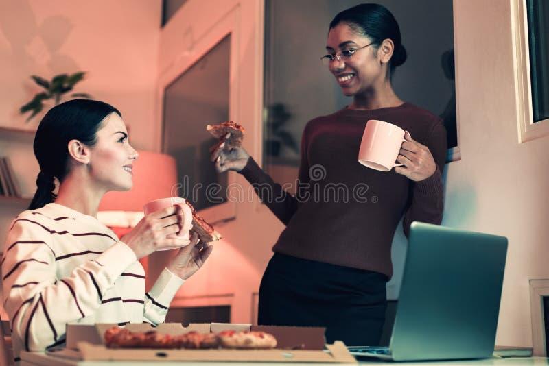 Όμορφα κορίτσια που τρώνε την πίτσα στο γραφείο στοκ εικόνες
