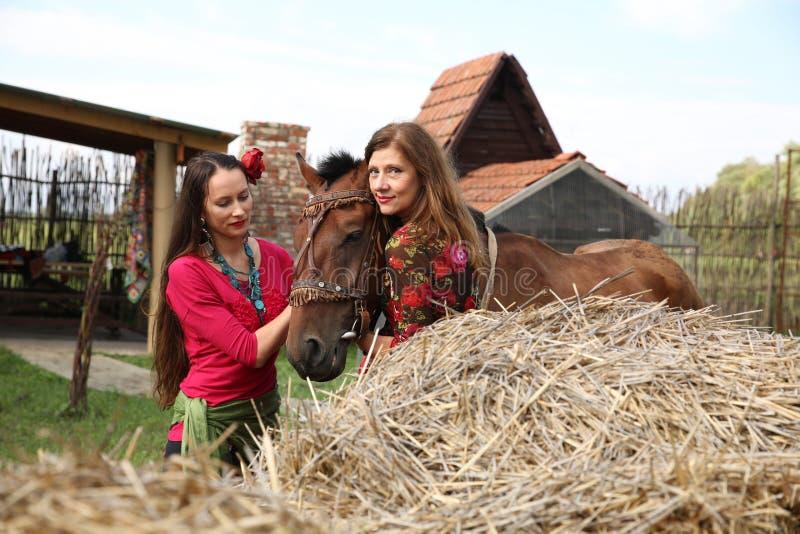όμορφα κορίτσια τσιγγάνων στα φωτεινά ενδύματα με ένα άλογο σε ένα αγρόκτημα στοκ φωτογραφία με δικαίωμα ελεύθερης χρήσης