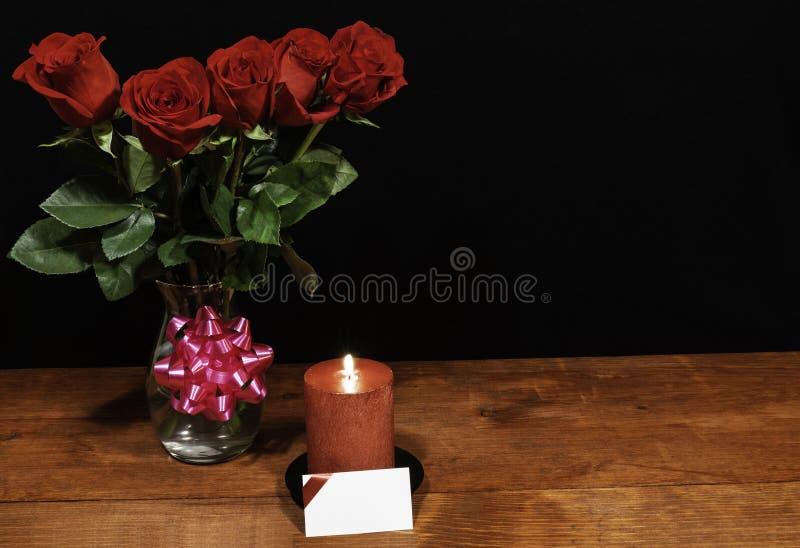 Όμορφα κόκκινα τριαντάφυλλα στο βάζο με το ρόδινο τόξο και το κόκκινο κερί στον ξύλινο πίνακα στο σκοτεινό υπόβαθρο στοκ εικόνες