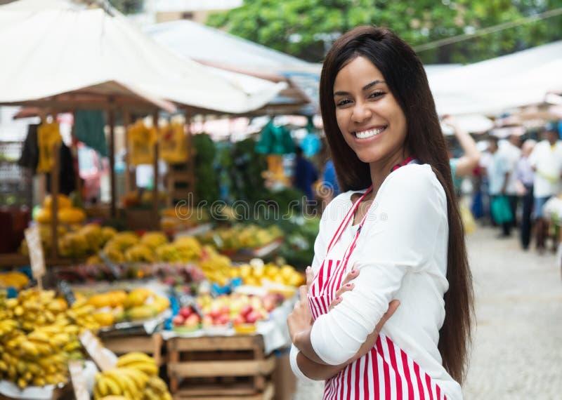 Όμορφα λατινοαμερικάνικα πωλώντας φρούτα γυναικών στην αγορά αγροτών στοκ εικόνα