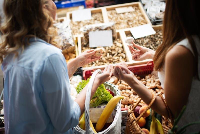 Όμορφα λαχανικά και φρούτα αγορών γυναικών στην αγορά στοκ εικόνες