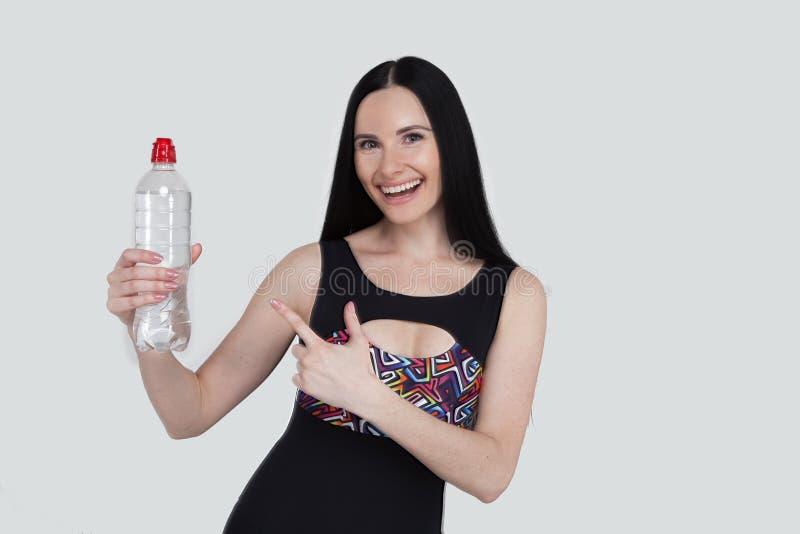 Όμορφα λεπτά αθλητικά ενδύματα νέων κοριτσιών brunette στο γκρίζο υπόβαθρο Φίλαθλο υγιές πρότυπο που δείχνει ένα μπουκάλι νερό πα στοκ φωτογραφία