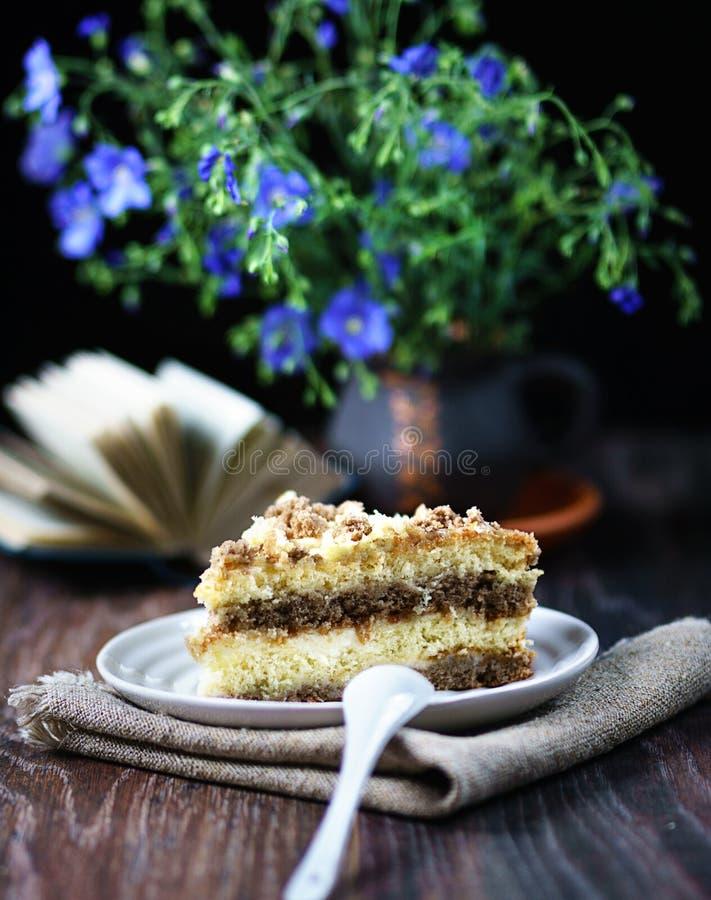 Όμορφα λουλούδια, ένα βιβλίο, και ένα εύγευστο κέικ καλή διάθεση στοκ φωτογραφία με δικαίωμα ελεύθερης χρήσης