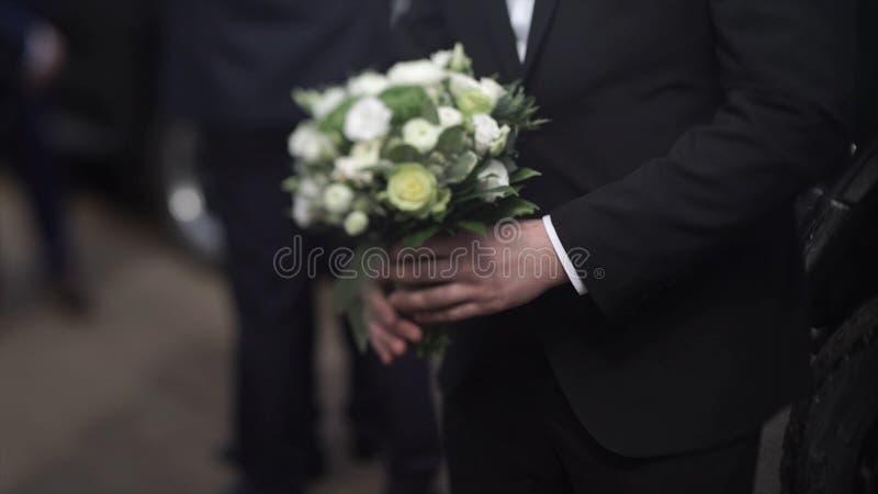 Όμορφα λουλούδια εκμετάλλευσης επιχειρηματιών Νεόνυμφος σε ένα κοστούμι που κρατά μια ανθοδέσμη των λουλουδιών Γαμήλια μπουτονιέρ στοκ εικόνα με δικαίωμα ελεύθερης χρήσης