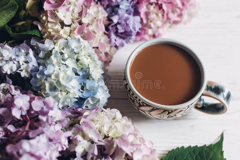 Όμορφα λουλούδια hydrangea και φλυτζάνι καφέ στο αγροτικό άσπρο ξύλο Ζωηρόχρωμο ρόδινο, μπλε, πράσινο hydrangea, ευχετήρια κάρτα  στοκ εικόνες