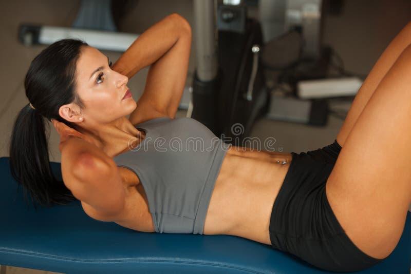 Όμορφα νέα κατάλληλα ABS μυών γυναικών workout κοιλιακά στο fitne στοκ εικόνα