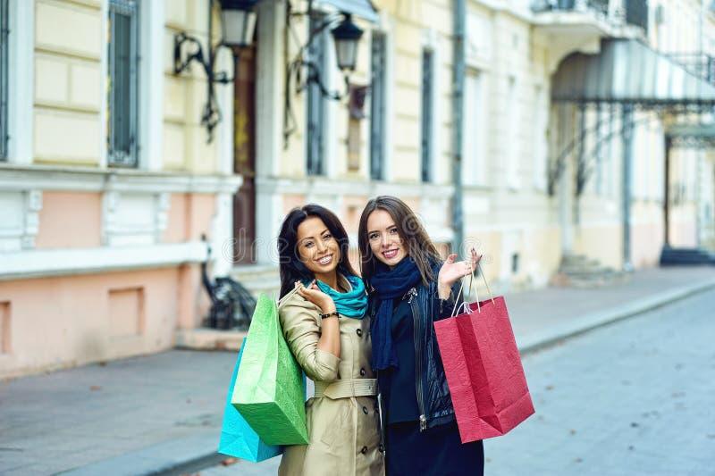 Όμορφα νέα κορίτσια που έχουν τη διασκέδαση στην πόλη που κάνει τις αγορές στοκ εικόνες με δικαίωμα ελεύθερης χρήσης