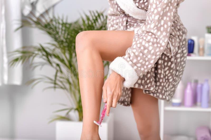 Όμορφα νέα πόδια ξυρίσματος γυναικών στο σπίτι στοκ εικόνα με δικαίωμα ελεύθερης χρήσης