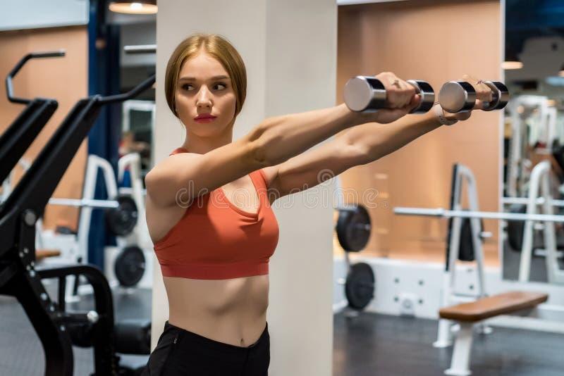 Όμορφα νέα τραίνα γυναικών δελτοειδή στη γυμναστική στοκ εικόνες