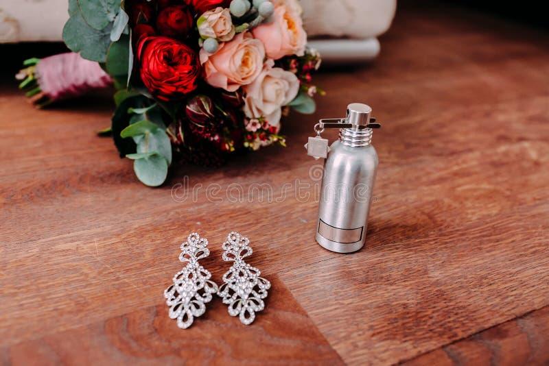 Όμορφα νυφικά σκουλαρίκια και άρωμα στο ξύλινο πάτωμα δίπλα στη γαμήλια ανθοδέσμη στοκ φωτογραφίες με δικαίωμα ελεύθερης χρήσης