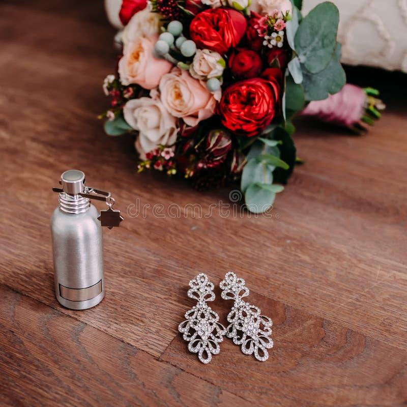 Όμορφα νυφικά σκουλαρίκια και άρωμα στο ξύλινο πάτωμα δίπλα στη γαμήλια ανθοδέσμη στοκ εικόνες