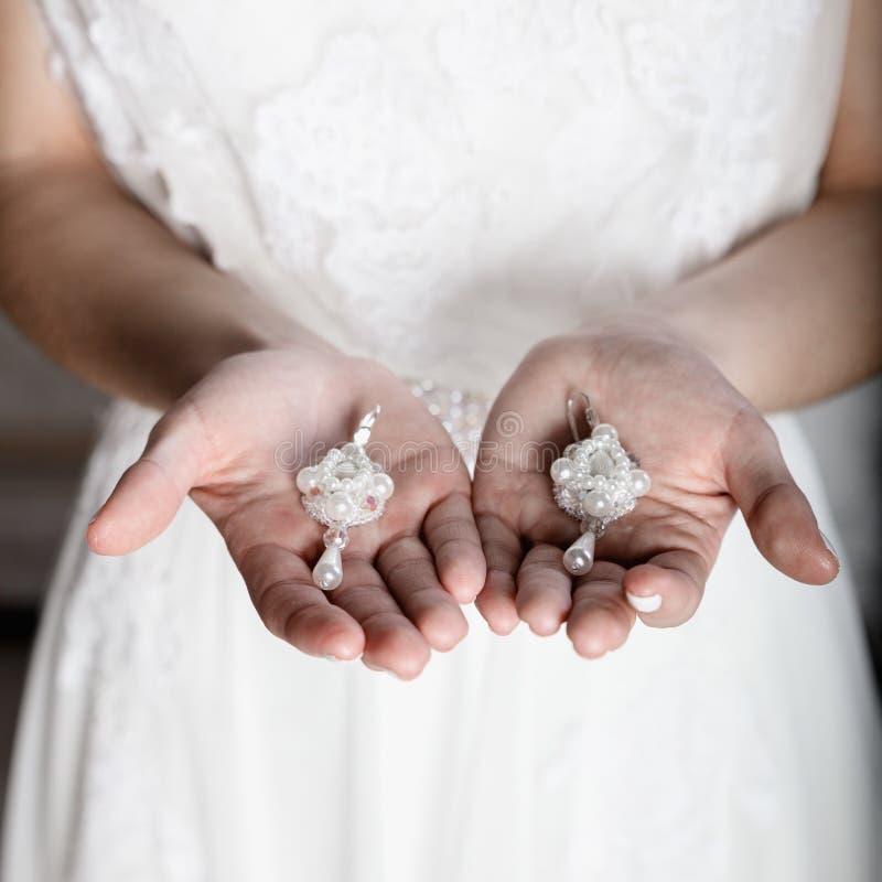 Όμορφα νύφη και σκουλαρίκια στα χέρια στοκ φωτογραφία