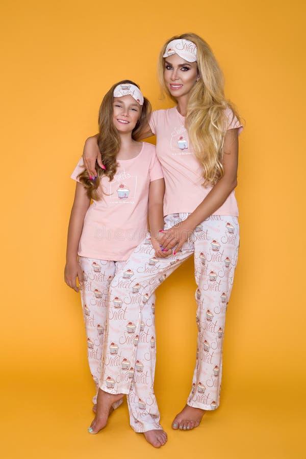 Όμορφα ξανθά κορίτσια, μητέρα με την κόρη στις πυτζάμες σε ένα κίτρινο υπόβαθρο στο στούντιο στοκ εικόνες