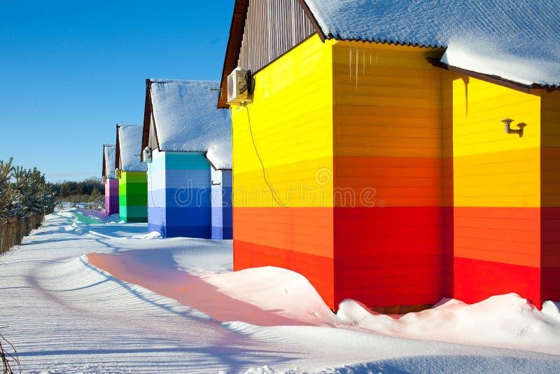 Όμορφα ξύλινα σπίτια που χρωματίζονται στα χρώματα ουράνιων τόξων Όμορφο ξύλινο υπόβαθρο Χειμώνας στοκ εικόνες