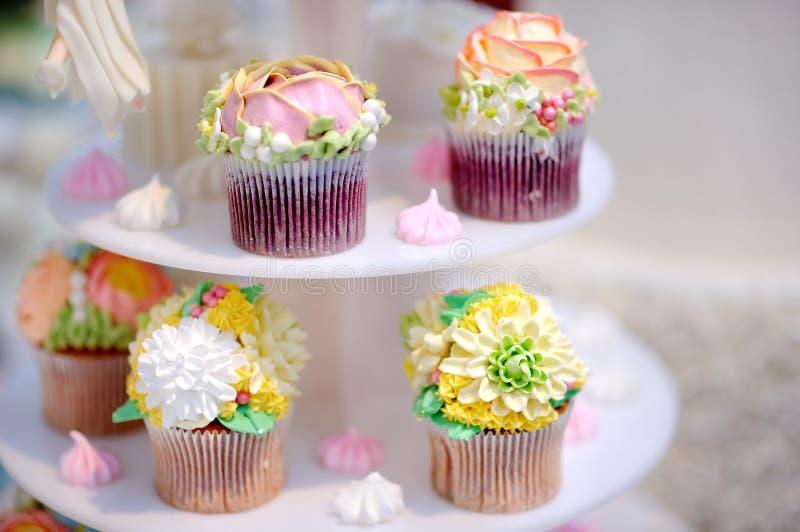 Όμορφα λουλούδια γαμήλιας cupcakes διακοσμημένα κρέμας στοκ εικόνες