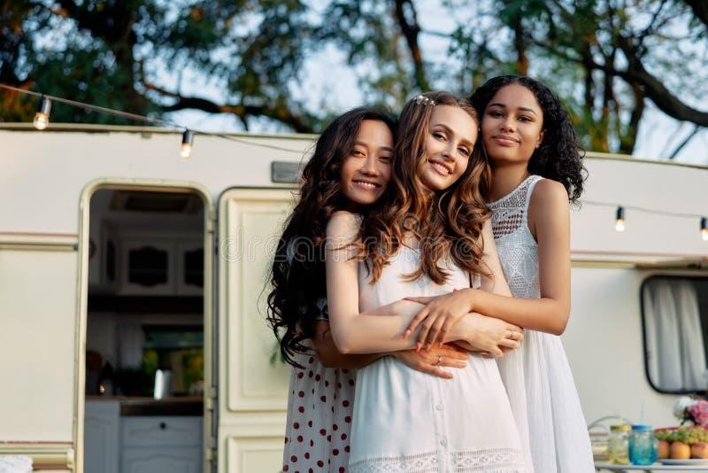 Όμορφα πολυεθνικά κορίτσια που αγκαλιάζονται κοντά στο κάπαρδο στοκ εικόνες με δικαίωμα ελεύθερης χρήσης
