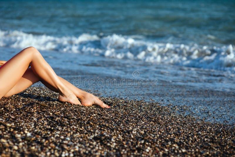 Όμορφα προκλητικά πόδια γυναικών ` s στην παραλία στοκ εικόνα