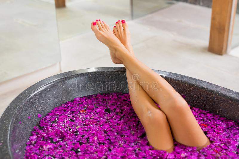 Όμορφα πόδια γυναικών ` s στο λουτρό λουλουδιών στοκ εικόνες