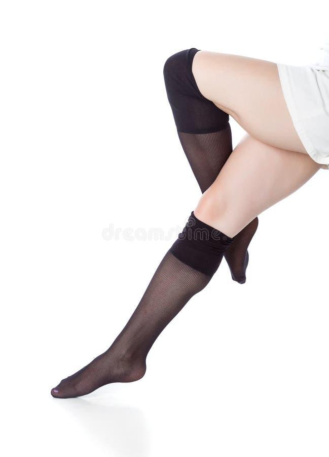 Όμορφα πόδια στις μαύρες γυναικείες κάλτσες στοκ εικόνα