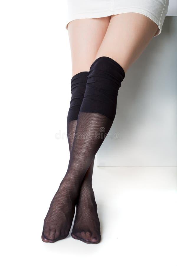 Όμορφα πόδια στις μαύρες γυναικείες κάλτσες στοκ εικόνες