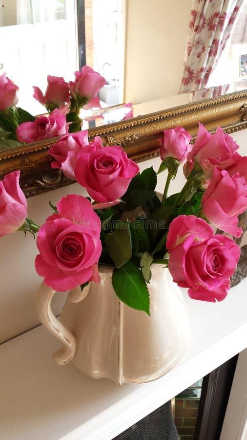 Όμορφα ρόδινα τριαντάφυλλα σε μια κανάτα κρέμας στοκ εικόνα