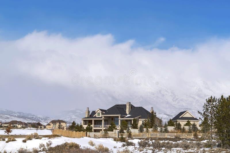 Όμορφα σπίτια σε μια γειτονιά που αγνοεί καλυμμένο το χιόνι βουνό το χειμώνα στοκ εικόνες με δικαίωμα ελεύθερης χρήσης