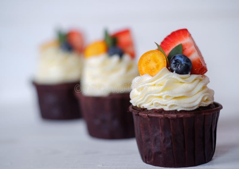 Όμορφα σπιτικά cupcakes με τις φράουλες στον άσπρο πίνακα στοκ φωτογραφίες