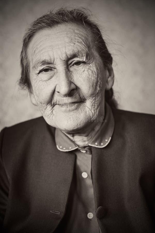 Όμορφα 80 συν τη χρονών ανώτερη τοποθέτηση γυναικών για ένα πορτρέτο στο σπίτι της στοκ φωτογραφία