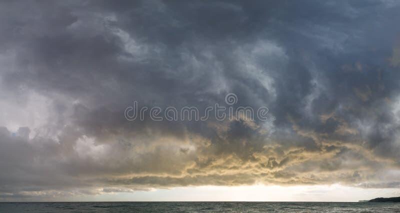 Όμορφα σύννεφα μολύβδου μπροστά από μια θύελλα εν πλω στο ηλιοβασίλεμα πανόραμα στοκ φωτογραφία με δικαίωμα ελεύθερης χρήσης