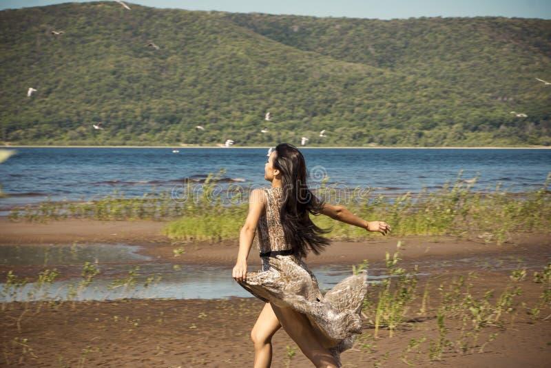 Όμορφα τρεξίματα νέων κοριτσιών κατά μήκος της παραλίας στοκ εικόνες