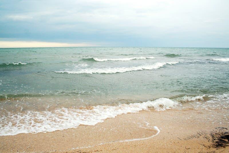 Παραλία άμμων και κύματα του κρυστάλλου - σαφή μπλε νερά στοκ εικόνα με δικαίωμα ελεύθερης χρήσης