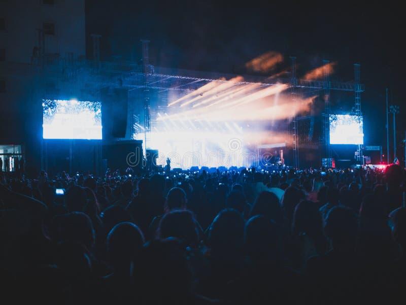 Όμορφα φω'τα από τη σκηνή σε μια μεγάλη συναυλία με το μεγάλο πλήθος στοκ εικόνα