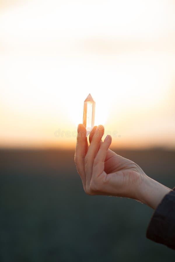 Όμορφα χέρια γυναικών που κρατούν τα κρύσταλλα λίγου χαλαζία στο φως του ήλιου στοκ φωτογραφία με δικαίωμα ελεύθερης χρήσης