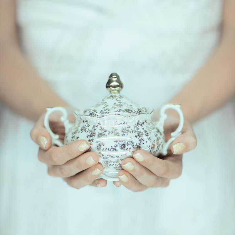 Όμορφα χέρια γυναικών που κρατούν το εκλεκτής ποιότητας παλαιό δοχείο ζάχαρης στοκ εικόνα με δικαίωμα ελεύθερης χρήσης