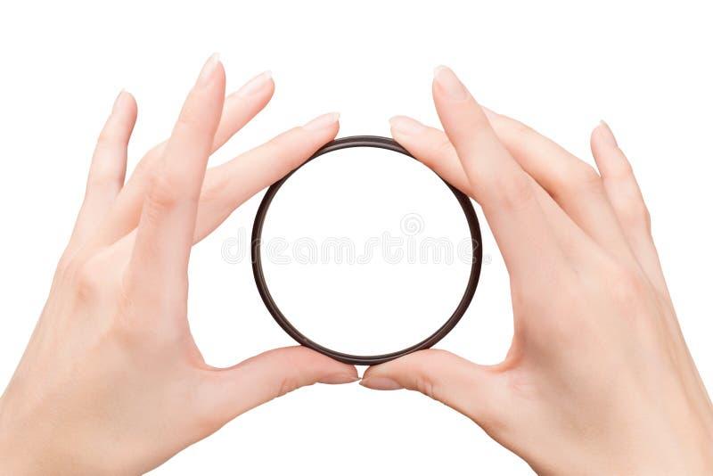 Όμορφα χέρια γυναικών που κρατούν το φίλτρο καμερών στοκ φωτογραφίες