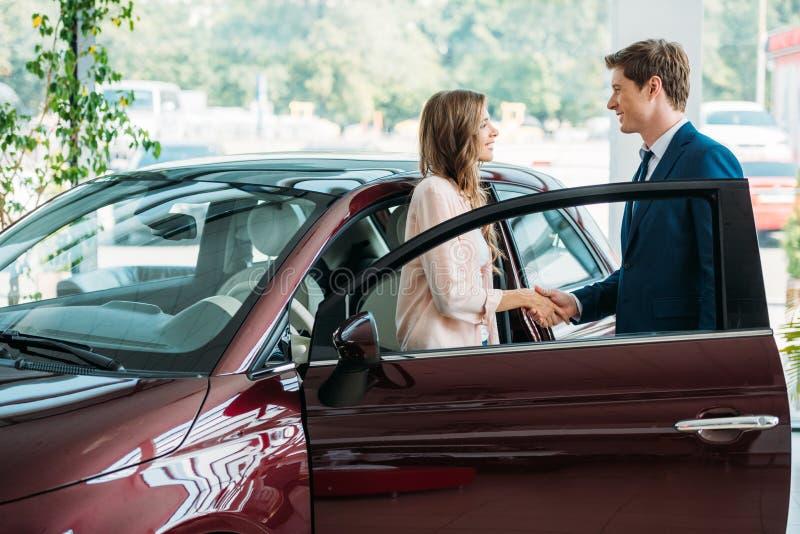 Όμορφα χέρια τινάγματος διευθυντών πωλήσεων στον πελάτη μετά από να πωλήσει ένα αυτοκίνητο στοκ φωτογραφίες
