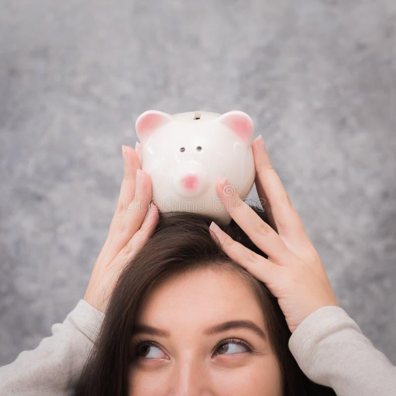 Όμορφα χρήματα αποταμίευσης νέων κοριτσιών για την περίοδο διακοπών, αποταμίευση στοκ φωτογραφία