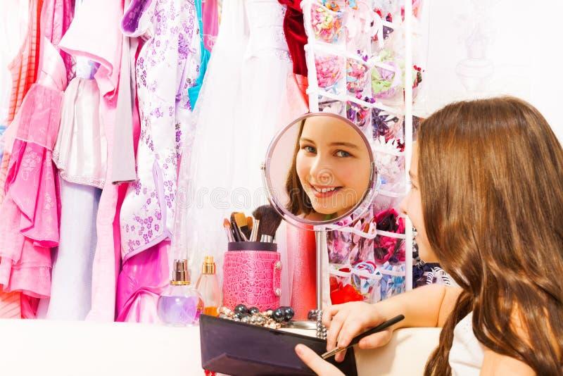Όμορφα όμορφα χαμόγελα κοριτσιών στο στρογγυλό καθρέφτη στοκ φωτογραφία