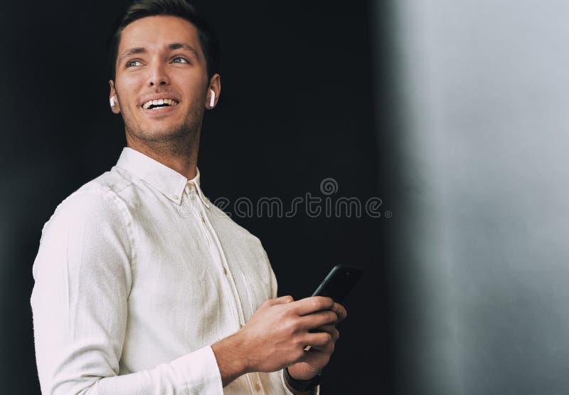 Όμορφα texting μηνύματα νεαρών άνδρων από το κινητό τηλέφωνο του πέρα από το μαύρο υπόβαθρο στούντιο, με τα ασύρματα ακουστικά στοκ φωτογραφία με δικαίωμα ελεύθερης χρήσης