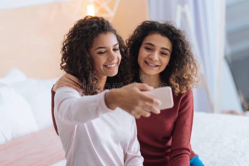 Όμορφες αδελφές που θέτουν για το selfie στο σπίτι στοκ εικόνα με δικαίωμα ελεύθερης χρήσης